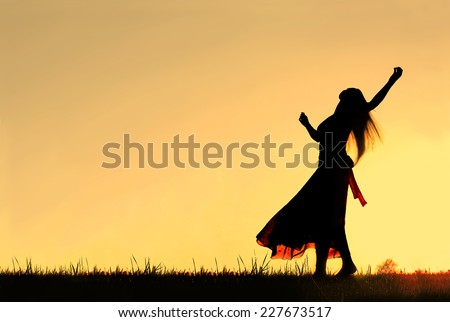 A woman wearing a long skirt, with long blonde hair, is dancing and spinning, while silhouetted against the evening sky - stock photo