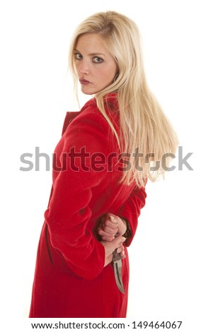 A woman wearing a red jacket is standing with a knife behind her back - stock photo