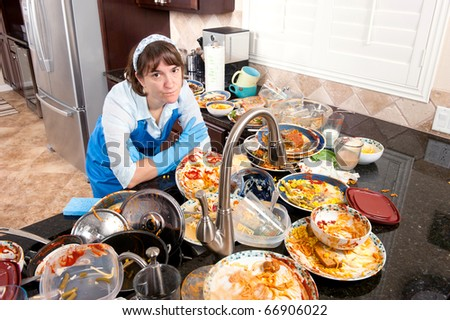 A woman wearing dish washing gloves and an apron contemplates doing the dishes. - stock photo