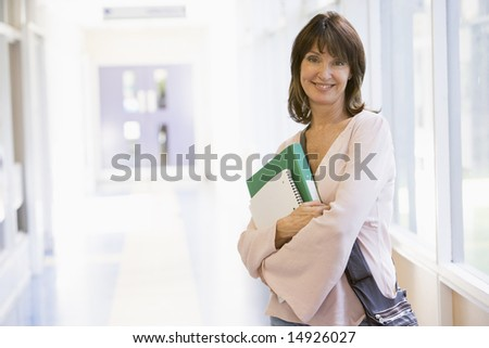 A woman with a backpack standing in a campus corridor - stock photo