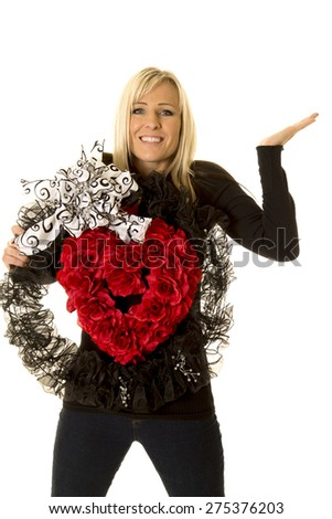 A woman with a big smile holding on to a wreath with a big red heart. - stock photo