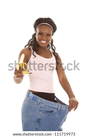 A woman with  a big smile on her face holding on to her banana and hanging on to her big pants. - stock photo