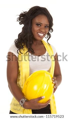 A woman with a big smile on her face holding on to her yellow hard hat. - stock photo
