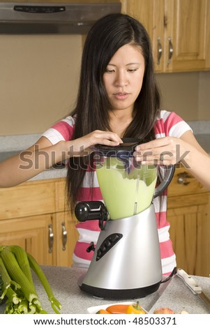 A woman with a blender making healthy food - stock photo