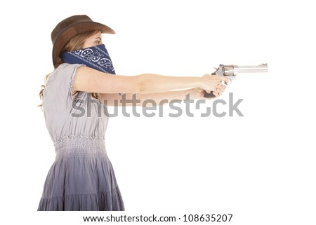 A woman with a blue bandanna around her mouth with her cowgirl hat on pointing a gun. - stock photo