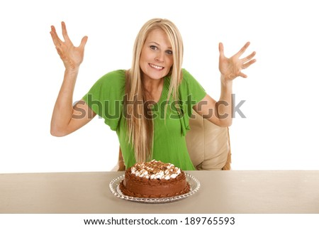 A woman with a cake on the table with her hands out and a smile on her lips. - stock photo