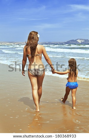 A woman with a child by the hand goes along the sea shore - stock photo