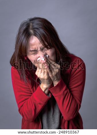 A woman with a cold blows her nose way too hard. - stock photo
