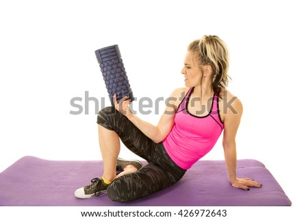 A woman with a confused expression on her face, holding up her roller. - stock photo