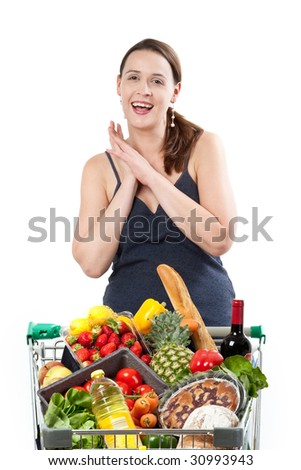 A woman with a full shopping cart happy to be shopping - clasping hands on a white background - stock photo