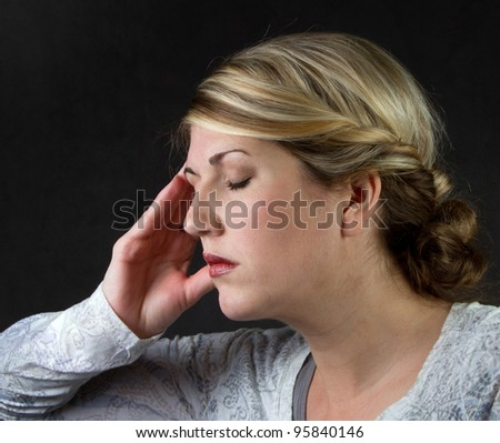 A woman with a headache against a dark background - stock photo