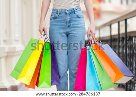 A woman with a lot of colourful shopping bags. - stock photo