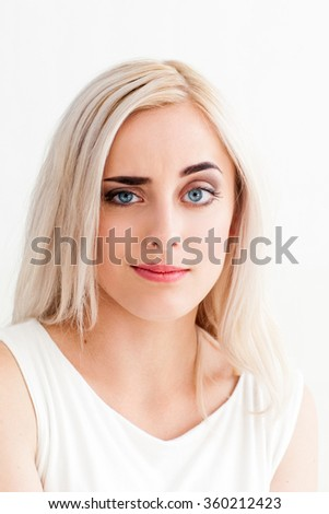 A woman with a raised eyebrow in surprise. The concept of misunderstanding, stupidity, bad joke, of mischief, nonsense. photo on the white background - stock photo