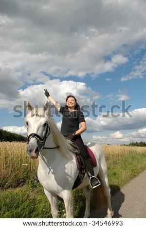 A woman with a raised hand sits on Andalusian horse. - stock photo