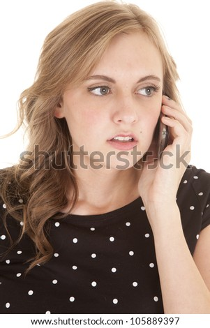a woman with a serious expression on her face holding her phone up to her ear. - stock photo