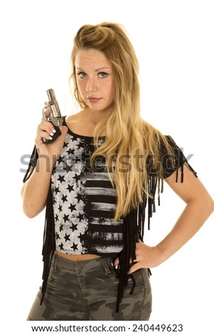 a woman with a serious expression on her face, holding on to a pistol. - stock photo