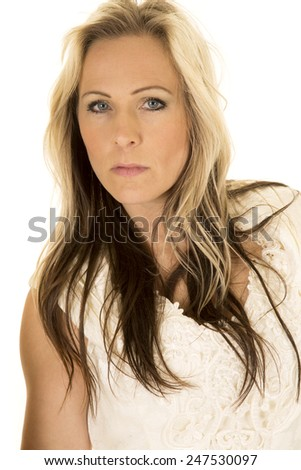 a woman with a serious expression on her face, in her wedding dress. - stock photo