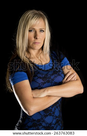 a woman with a serious expression on her face, with her arms folded. - stock photo
