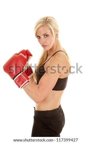 a woman with a serious expression wearing boxing gloves. - stock photo