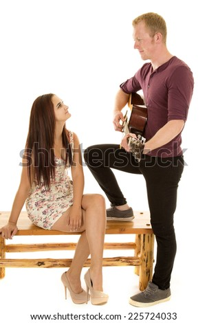 A woman with a smile on her face, enjoying her man playing the guitar. - stock photo