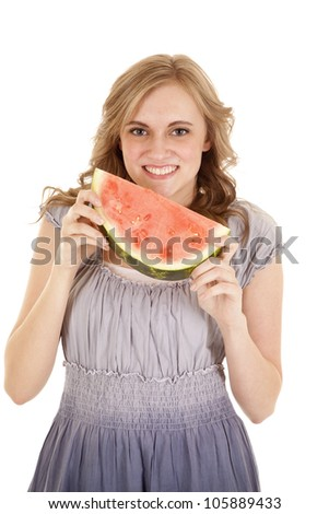 A woman with a smile on her face holding on to her piece of watermelon. - stock photo