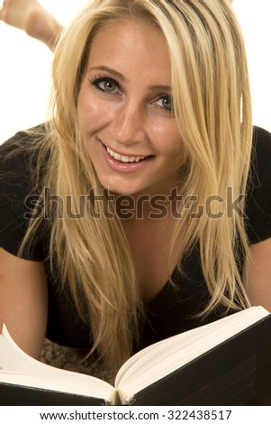 A woman with a smile reading a book, laying on the carpet. - stock photo