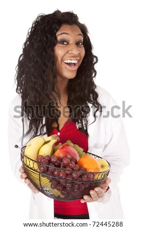 A woman with a stethoscope is holding a fruit basket. - stock photo