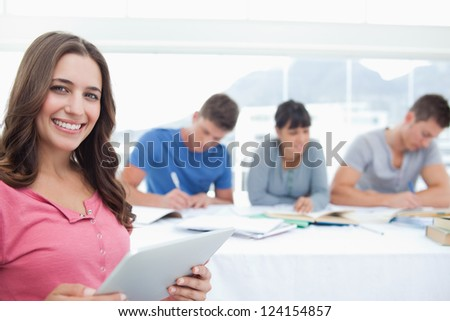 A woman with a tablet pc in her hands as she smiles and looks at the camera while her friends sit together in the background - stock photo