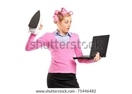 A woman with hair rollers holding an iron and looking at laptop isolated on white background - stock photo
