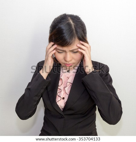 A woman with headache, migraine, stress, hangover in business executive dress, office syndrome concept - stock photo