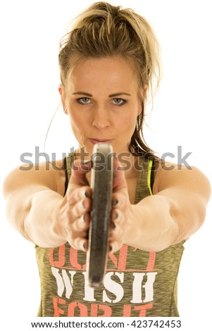 A woman with her arms out, holding onto a weight, with a serious expression on her face. - stock photo
