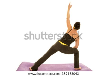 A woman with her back to the camera doing a yoga stretch. - stock photo