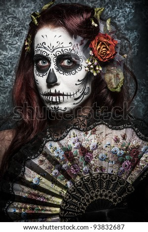 a woman with her face painted as a traditional day of the dead sugarskull mask - stock photo