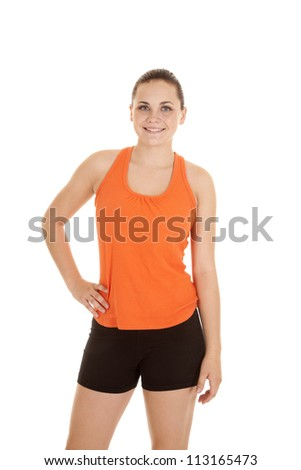 A woman with her hand on her hip with a smile on her lips in her fitness clothes. - stock photo