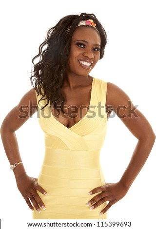 a woman with her hands on her hips in a yellow dress with a smile on her face. - stock photo