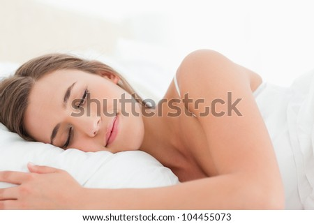 A woman with her head on the pillow sleeping in bed. - stock photo