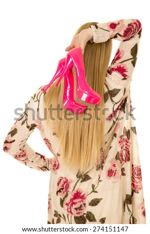 A woman with her pink shoes holding them by her head. - stock photo