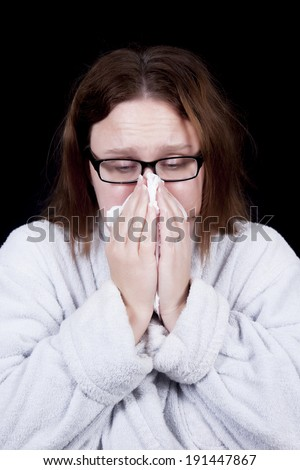 A woman with messy hair blows her nose as she suffers from a cold or the flu.  She wears glasses and a bathrobe. - stock photo