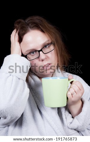A woman with messy hair holds her head suggesting a headache.  In her other hand is a coffee mug with hot tea.  She wears glasses and a bathrobe. - stock photo