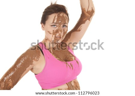 A woman with mud all over her body with a serious expression on her face. - stock photo