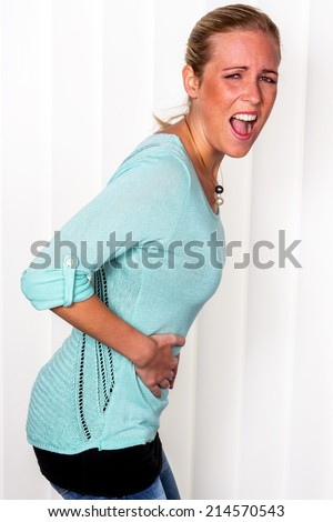 a woman with pain in the abdomen curves. - stock photo