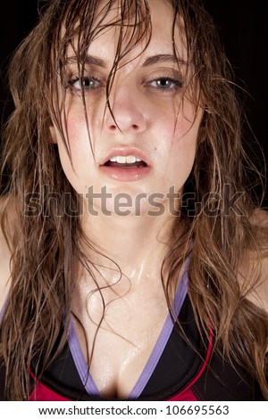 A woman with sweat running down her face after a workout. - stock photo