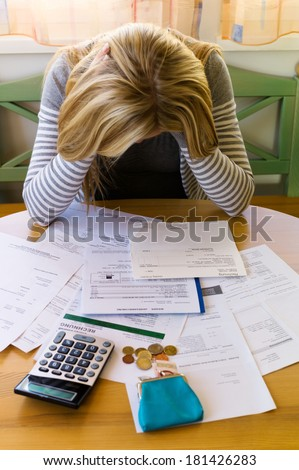 a woman with unpaid bills has many debts. unemployment and personal bankruptcy - stock photo