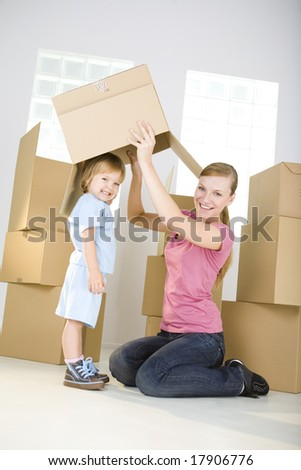 A woman with young girl are between cardboard boxes. A woman taking off cardboard box from head young girl. They're looking at camera. - stock photo