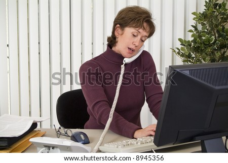 A woman working at her computer in multi-tasking mode. - stock photo