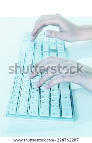 a woman working in an office on the keyboard of a computer - stock photo