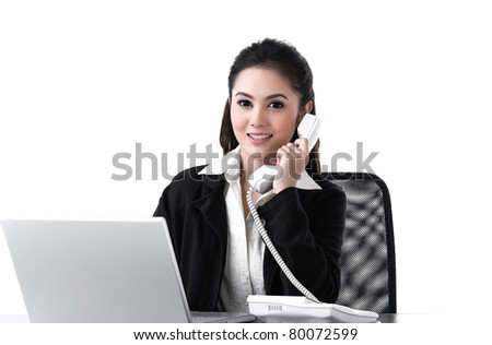 A woman working on laptop and talking on the phone - stock photo