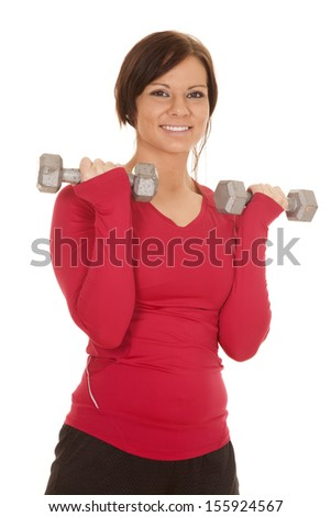 A woman working out her arms with weights and a smile on her face. - stock photo