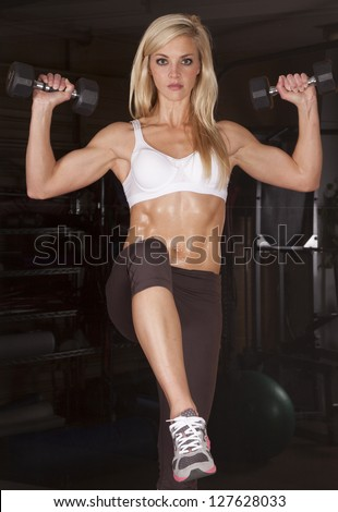 A woman working out in a gym lifting weights with a serious expression on her face. - stock photo
