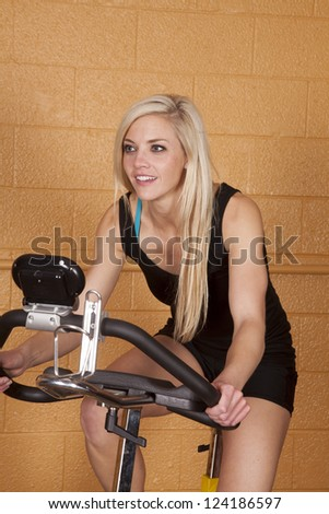 A woman working out in a gym on a bike with a smile on her face. - stock photo